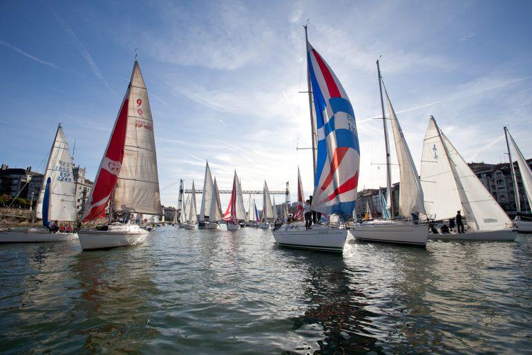 Barcos participantes en la Regata del Gallo navegan bajo el Puente Colgante