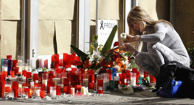 A woman lights a candle in memory of the teacher who yesterday resulted killed at the Joan Fuster Institute in Barcelona, on April 21, 2015. A 13-year-old boy armed with a crossbow and knife killed a teacher and wounded four others at his school in Barcelona on April 20, 2015 before being subdued, police and witnesses said. Among the injured were a Spanish language teacher and her daughter, also a student at the school, according to Spanish media reports.   AFP PHOTO / QUIQUE GARCIA