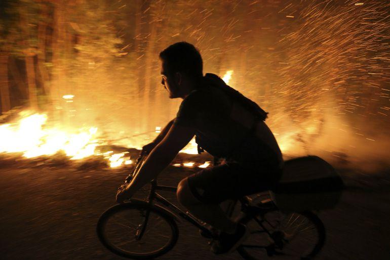Un vecino intenta sofocar las llamas del incendio forestal de Arbo (Pontevedra), en el que se ha decretado la Situación 2 por la cercanía del fuego a núcleos de población. Las hectáreas de monte afectadas por los incendios forestales que se mantienen activos en Galicia son 5.500 según los últimos datos facilitados por la Xunta.