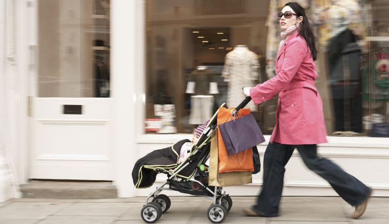 Una madre empuja el carrito con su hijo.