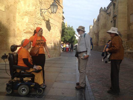 Victoria, una de las afectads, explica a los turistas el motivo de la movilización de hoy