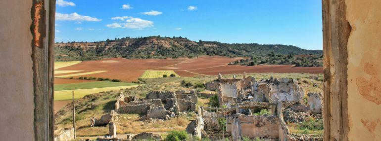 Casas derruidas en Villalbilla con el paisaje alcarreño al fondo.