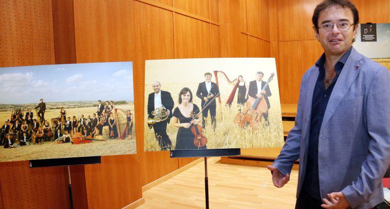 El director de l'OJC Terres de Lleida, Alfons Reverté, mostrant dues de les fotografies que s'han fet els músics de l'orquestra amb motiu del 15è aniversari, el 26 d'octubre de 2016.