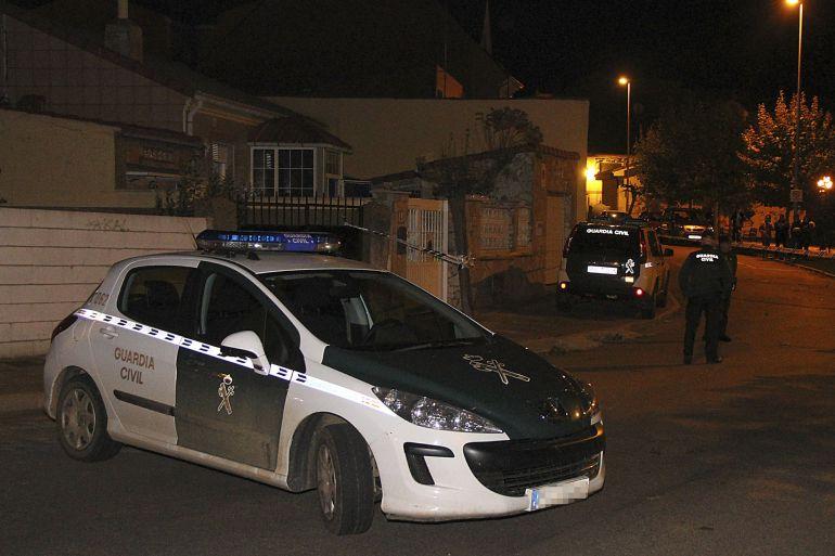 Un coche de la Guardia Civil junto a la vivienda donde aparecieron los cadáveres