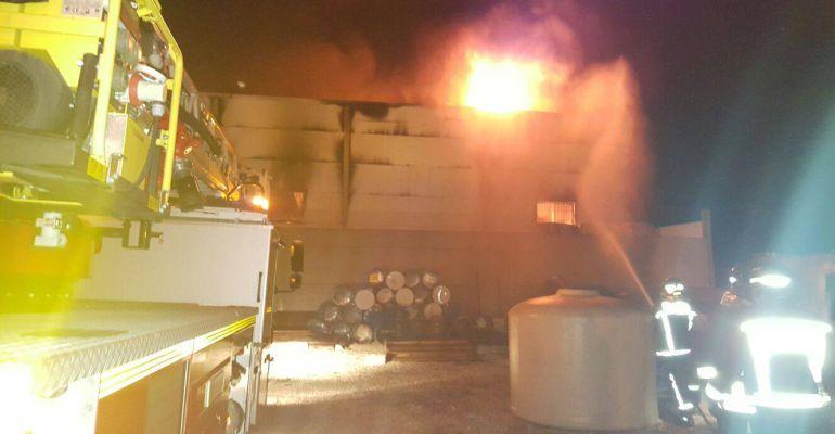Varios bomberos trabajando para extinguir el incendio que ha afectado a una nave en Andújar.
