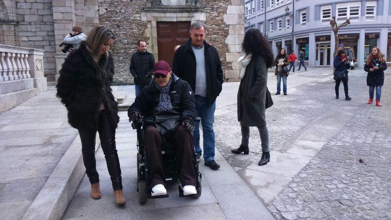 Una persona en silla de ruedas transitando con Lara Méndez por la Praza da Soidade