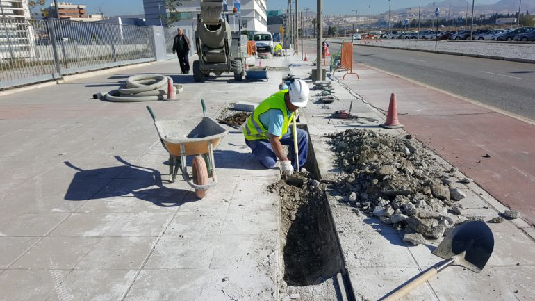 Un obrero de la construcción en Granada realiza trabajos en una acera de la zona del PTS el pasado noviembre