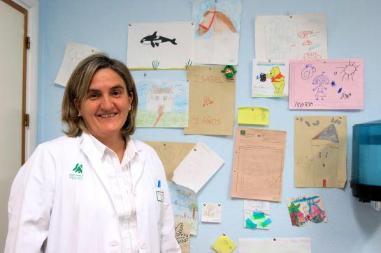 Auxiliadora Mazuecos posa junto a los dibujos colgados en la consulta de Nefrología