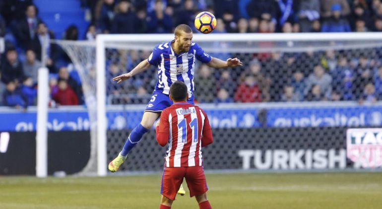 Víctor Laguardia despeja un balón de cabeza en presencia de Correa.