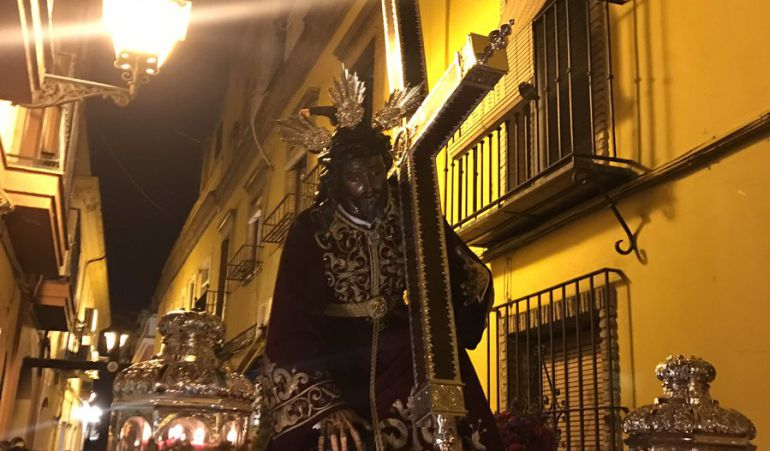 El Cristo de las Tres Caídas por la calle que lleva su nombre en el vía crucis que le ha llevado esta noche hasta la Parroquia de Santa Ana