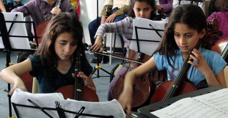 Dos niñas tocan un violonchelo durante un curso de formación de la Fundación Baremboim-Said.