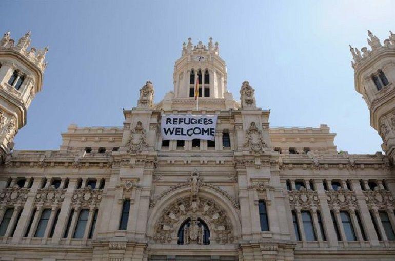 Imagen de la fachada del Ayuntamiento de Madrid, con una pancarta en apoyo a los refugiados