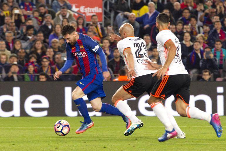 GRA451. BARCELONA. El delantero argentino del FC Barcelona Lionel Andrés Messi (i) se escapa del tunecino Aymen Abdennour (c), del Valencia CF, para marcar su segundo gol, durante el partido de la vigésimo octava jornada de Liga en Primera División que FC Barcelona y Valencia CF juegan esta tarde en el estadio del Camp Nou, en Barcelona. EFE, MARTA PÉREZ