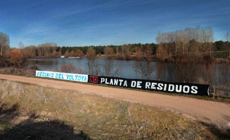 Pancarta contra la planta de residuos, colocada por los vecinos de Aldeanueva del Codonal, en la ribera del río Voltoya.