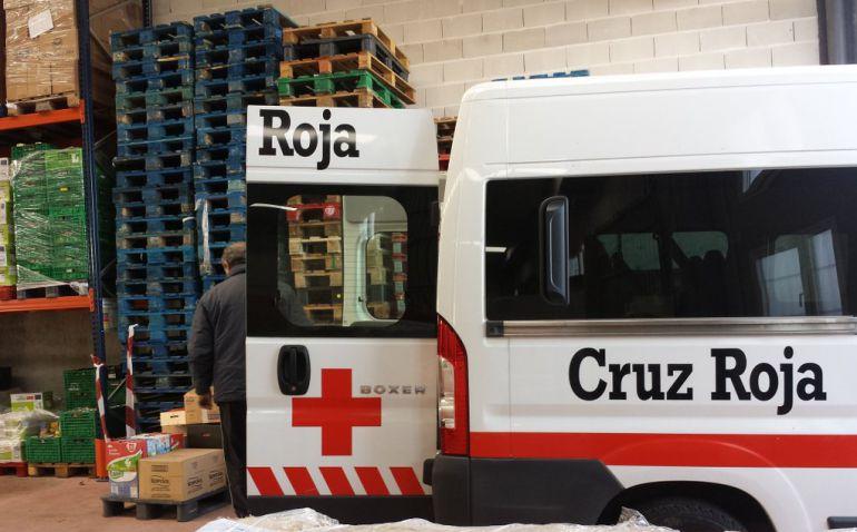 Una furgoneta de Cruz Roja carga comida en la nave del Banco de Alimentos