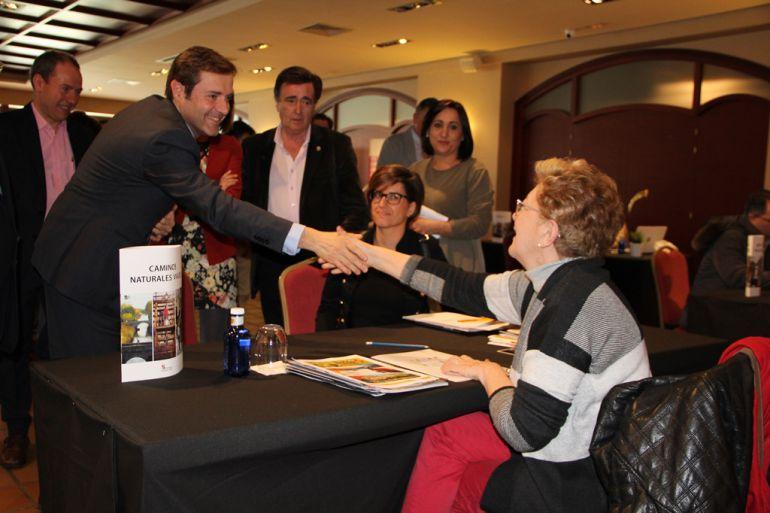El director general de turismo, saluda a una de las participantes en la jornada de comercial que se ha celebrado en Cuéllar.