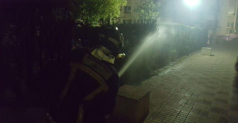 Un bombero apaga el fuego de un seto en el residencial Gran Avenida.