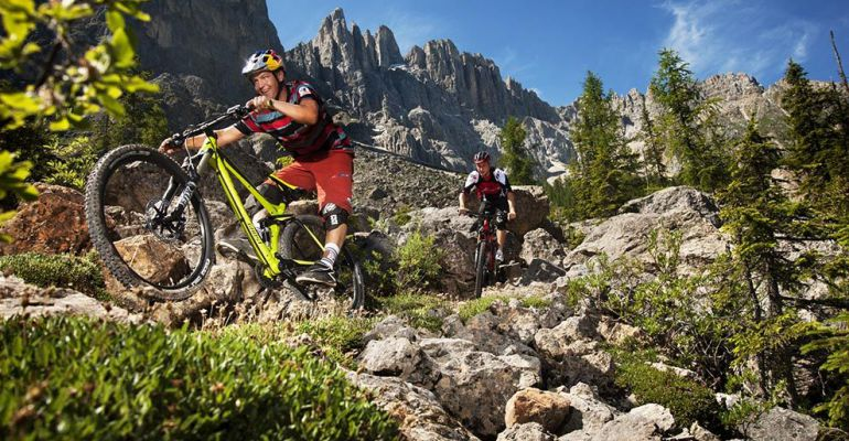 Dos ciclistas subidos en una mountain bike.