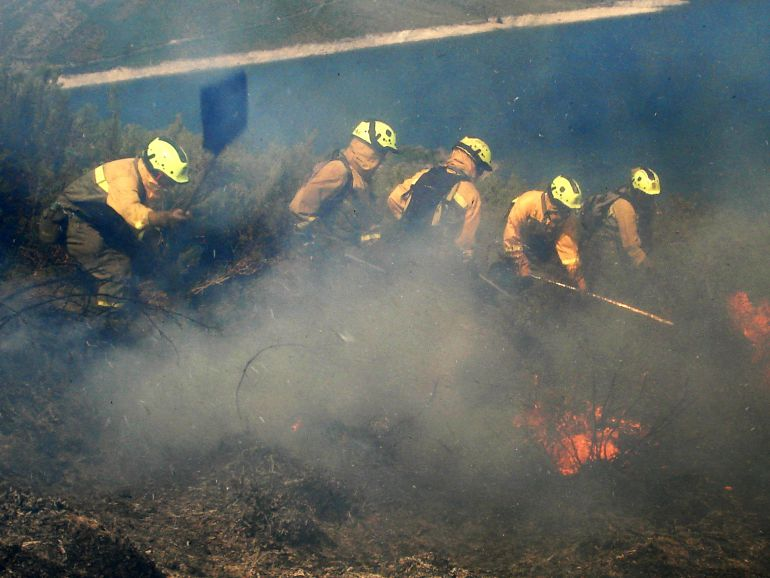 Las brigadas trabajan en la extinción de la lengua de fuego que se reaviva por las rachas de viento