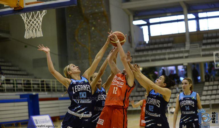Marinacci (00), Justel (13) y Espín (12) luchan por un balón en el último partido en casa ante Valencia Basket, ante la mirada de Marta Pérez (14)