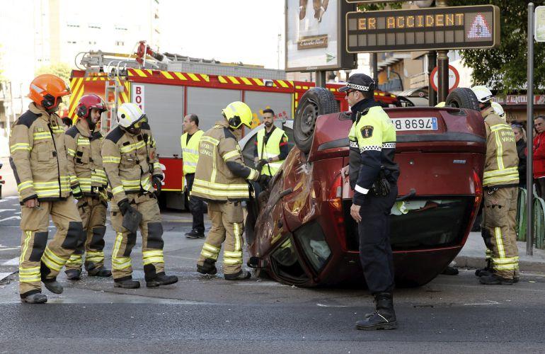 La unidad de bomberos junto a uno de los tres vehículos implicados en el accidente múltiple en la ciudad de Valencia, que se ha saldado con tres heridos leves. EFE.Juan Carlos Cárdenas