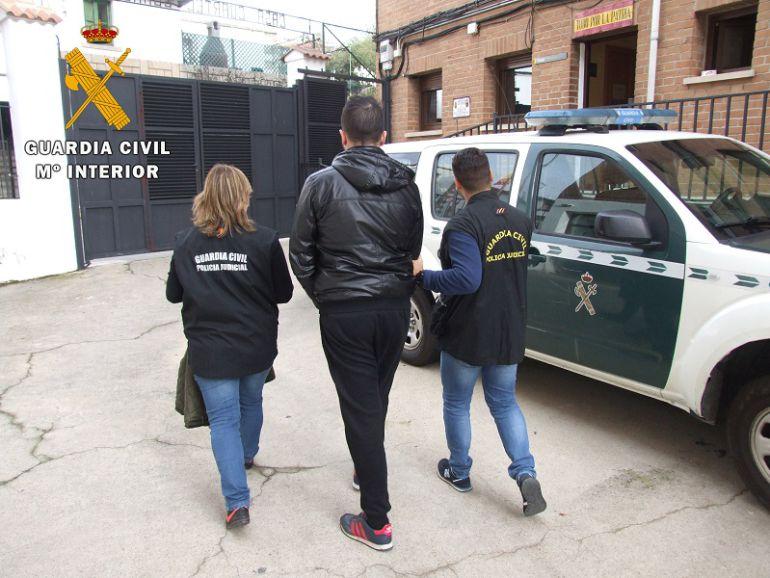 Agentes de la Guardia Civil acompañan a uno de los detenidos en la denominada Operación Ajuste