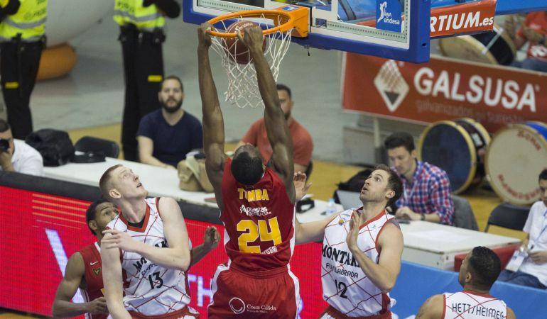 El pívot belga de UCAM Murcia, Kevin Tumba (c), hace un mate ante la mirada de los jugadores de Montakit Fuenlabrada, el ala pívot David Wear (i) y el alero Rolands Smits (2d), durante la derrota naranja en Murcia.