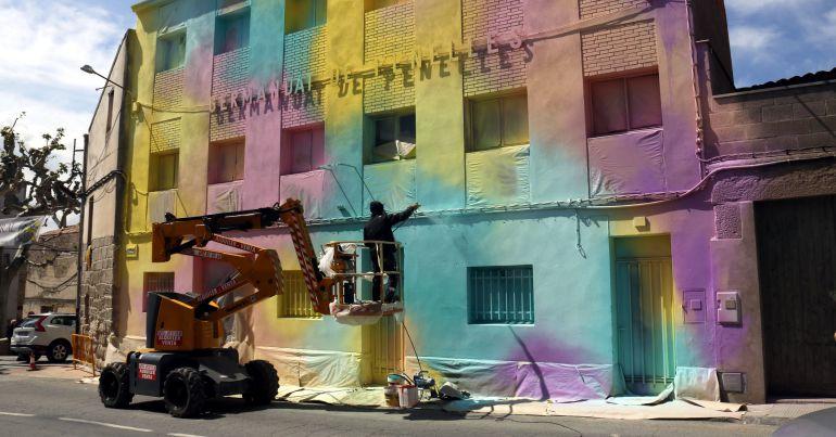 Un artista pintant la façana de l'edifici de la Germandat de Penelles en el marc del segon Festival Gar Gar el 20 d'abril de 2017