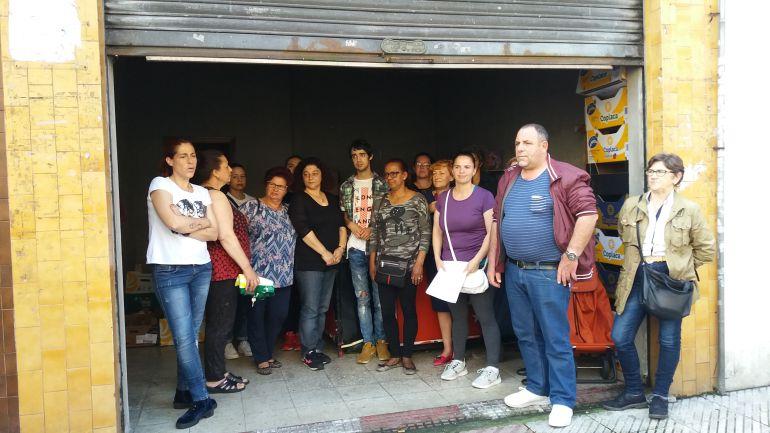 Miembros de la Plataforma por una Vivienda Digna y de la Asociación de Vecinos San Pedrín de Ventanielles ante el local que tienen alquilado para el reparto de alimentos.