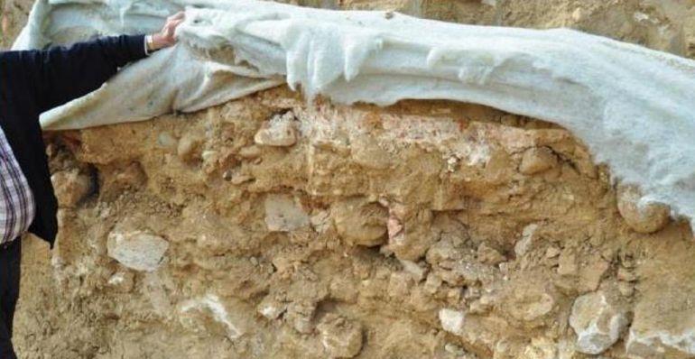 Imagen de los restos protegidos por una capa geotextil destrozada por las obras de la autovía