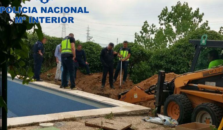 Agentes de la Policía Nacional buscando en el jardín del presunto autor del asesinato