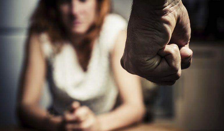 Una mujer se enfrenta con la mirada al puño de su agresor.