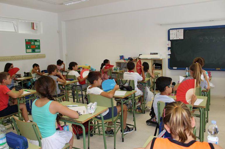 Algunos niños utilizan abanicos en el interior de una de las clases del colegio San José Obrero para sofocar el calor