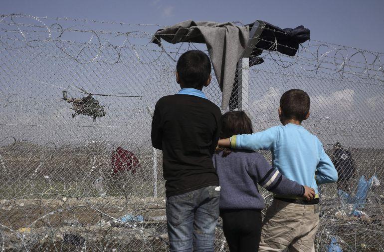 Tres niños frente a una valla en un campo de concentración