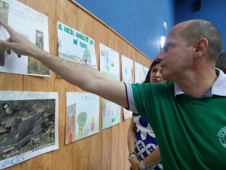 El alcalde y la delegada observan los trabajos presentados por los escolares