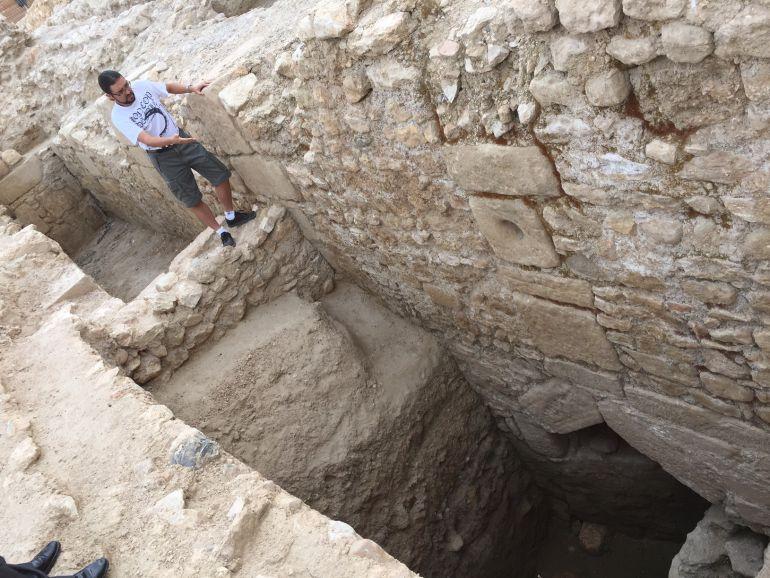 El director de les excavacions, Ramon Ferré, mostra, a sota de la imatge a la dreta, la sortida d'una claveguera d'època romana.