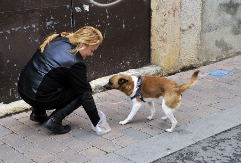 Una mujer recoge los excrementos de su mascota.