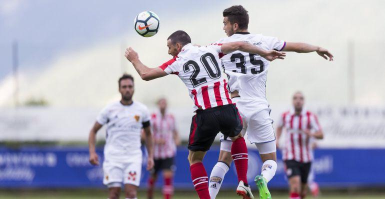 El delantero del Athletic de Bilbao, Aritz Aduriz (i) lucha por el balón con el Pedro Pacheco (d) del Basilea durante un amistoso que se disputa en el estadio de Cristo Rey en Lens, Suiza hoy 12 de julio de 2017
