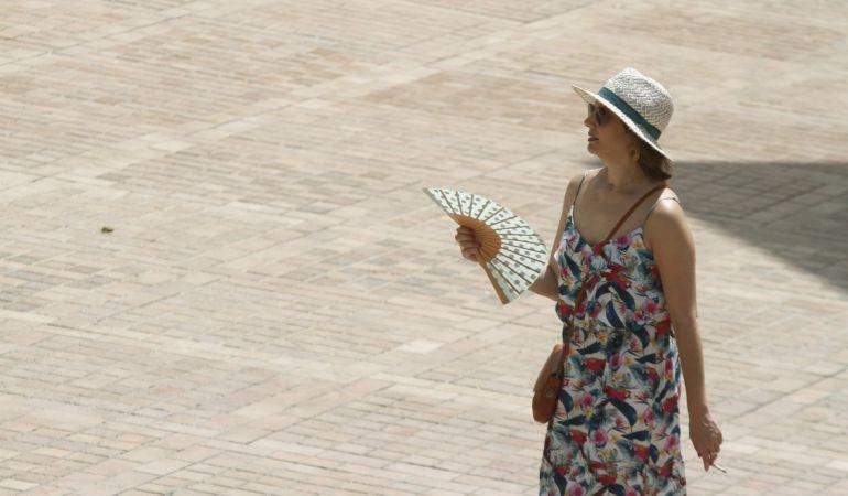 Una mujer se abanica mientras camina