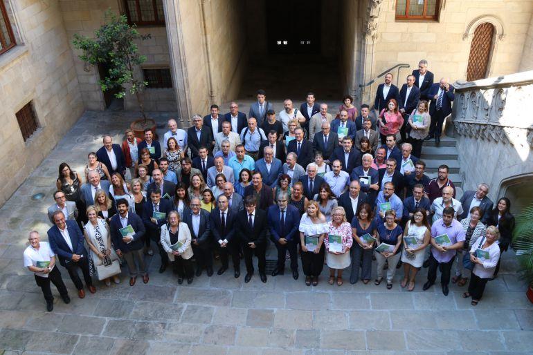 Fotografía de familia con todas las entidades firmantes del Pacto para la Reforma Horaria y el consejero de Presidencia, Jordi Turull, y el presidente de la Generalitat, Carles Puigdemont