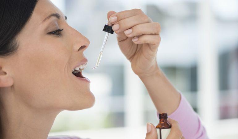 Mujer tomando medicina homeopática