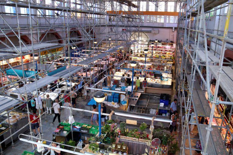 L'interior del mercat municipal d'Amposta amb les bastides instal·lades enmig de l'activitat normal dels paradistes.