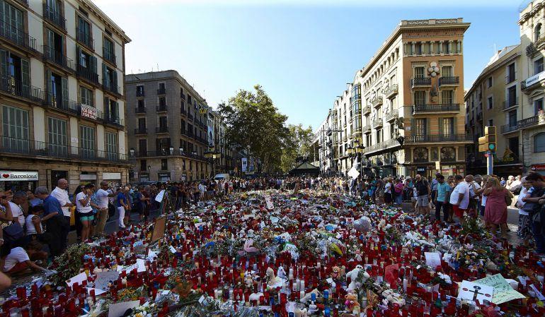 Cientos de personas se congregan en La Rambla de Barcelona, en el mosaico de Miró, lugar donde los ciudadanos depositan velas, flores y mensajes de apoyo y recuerdo a las víctimas del atentado del pasado jueves.