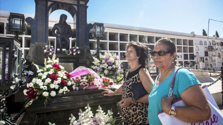 Dos mujeres pasan ante la tumba de Camarón