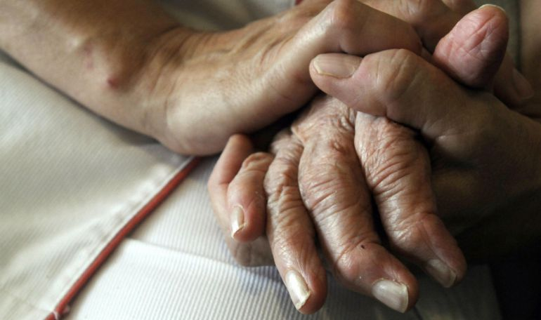 Una persona cuidadora sostiene la mano de un anciano