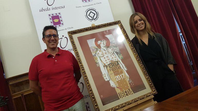 Jerónimo García y Tíscar Espadas, junto al cartel anunciador de la Feria de Úbeda