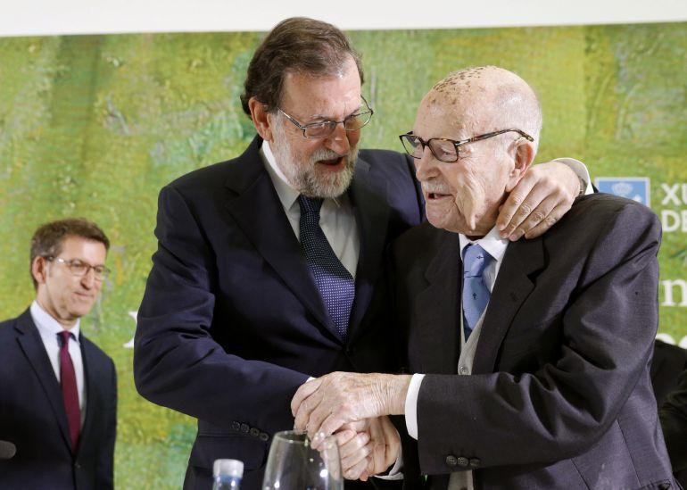 El jefe del Ejecutivo, Mariano Rajoy, abraza al primer presidente electo de la Xunta de Galicia, Xerardo Fernández Albor, que ha cumplido cien años, antes de imponerle la Medalla de Oro al Mérito en el Trabajo, junto al presidente de la Xunta, Alberto Núñez Feijóo