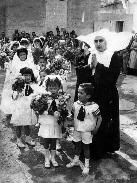 Niños de la Casa de Beneficencia con flores a María.