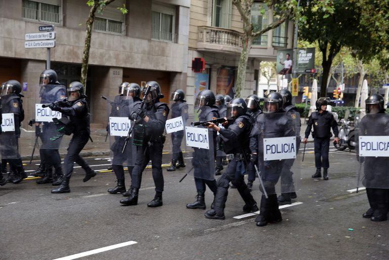 Agentes de la Policía Nacional apuntan con sufiles de balas de goma a los manifestantes en Barcelona, el 1 de octubre
