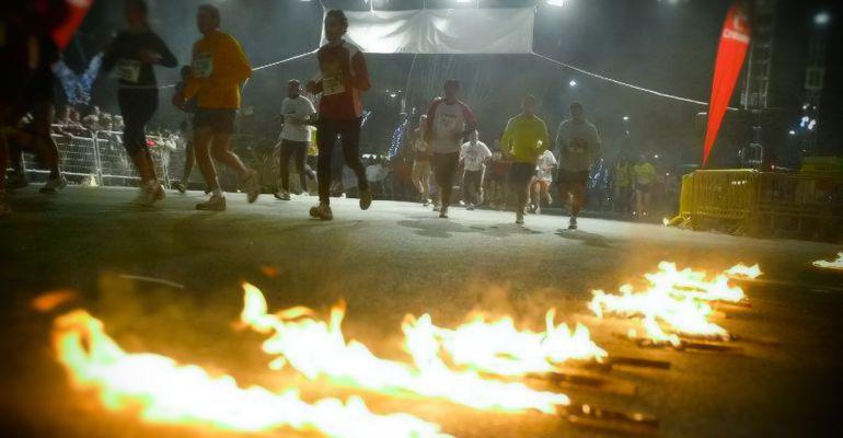 Atletas corren la San Antón iluminados por las antorchas de fuego.